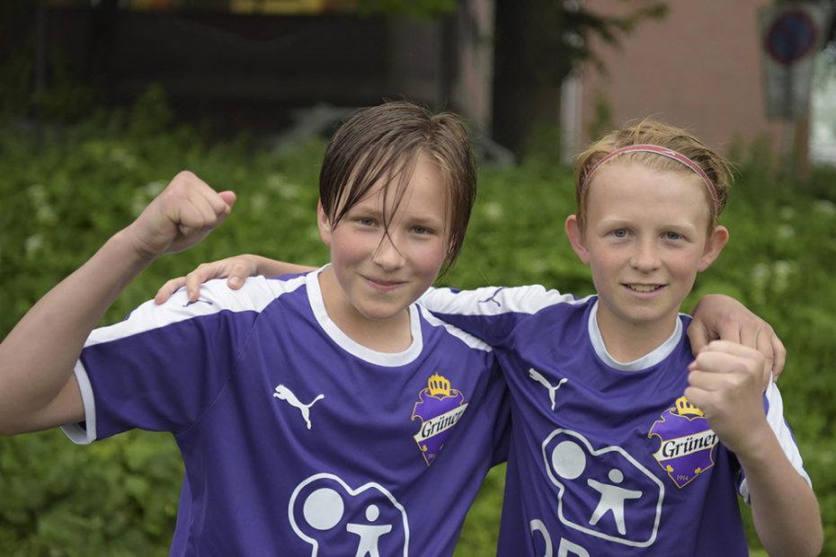 To spillere på Grüner Fotball smiler og holder hverandre over skuldrene